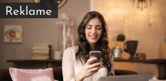 En kvinde med en smartphone i hånden og en computer i skødet